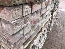 Telha vermelha do cimento da pedra de pavimentação para colocar a construção de estradas, pavimento em páletes de madeira em um c fotos de stock