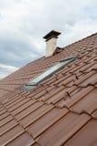 Telhado com claraboia, a telha vermelha natural e a chaminé Imagem de Stock