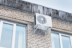 Telhado da casa e condicionamento de ar nos sincelos fotografia de stock royalty free
