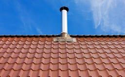 Telhado de telha vermelha com uma chaminé da lata Fotografia de Stock