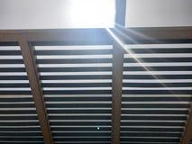 Telhado elegante do desenhista moderno sob o céu aberto com furos dos feixes com placas contra o sol fotos de stock royalty free