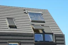 Telhado moderno da casa com aquecedor de água solar, os painéis solares e as claraboias Aquecimento de painel solar da água Imagens de Stock Royalty Free