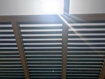 Telhado moderno do desenhista no ar livre com furos dos feixes com placas contra o sol foto de stock