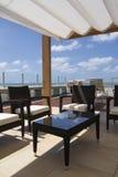 Telhado na frente do mar com camas bronzeadas, armchais, o céu azul e as nuvens brancas Imagens de Stock Royalty Free