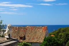 Telhado telhado com uma estátua de um leão Fotografia de Stock Royalty Free