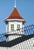 Telhado vermelho atrás da cerca Fotos de Stock Royalty Free