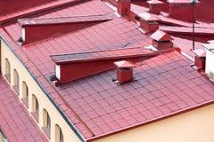 Telhado vermelho telhado do metal com chaminés e janelas Imagens de Stock