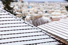 Telhados cobertos de neve inverno, hora para férias em uma cidade no contexto do borrão da geada, fim acima, detalhe Imagens de Stock Royalty Free