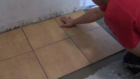 Telhas de assoalho da configuração do trabalhador manual em casa Tiro do close up vídeos de arquivo