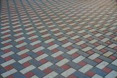 Telhas de pavimentação modeladas cinzentas, brancas e vermelhas com base na rua, opinião de perspectiva foto de stock