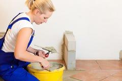 Telhas fêmeas da telha do tiler no assoalho foto de stock royalty free
