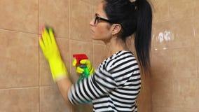Telhas limpas da mulher com esponja filme
