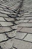 Telhas más e ondulando velhas do telhado em uma casa ou em uma casa Imagem de Stock