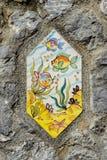 Telhas pintados à mão com os peixes em paredes da rua de Vietri foto de stock royalty free