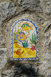 Telhas pintados à mão com os peixes em paredes da rua de Vietri imagem de stock