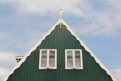 Telhe o detalhe de uma casa de madeira da Holanda na cor verde com as duas janelas brancas em um céu azul Fotos de Stock