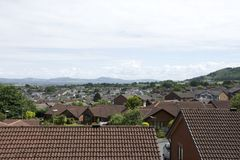 Telhe partes superiores da vila de Abergele em Grâ Bretanha com o campo circunvizinho, montanhas, montes e o céu azul e as nuvens Imagem de Stock