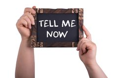 Tell me now. A woman holding chalkboard with words tell me now isolated on white background Royalty Free Stock Photo