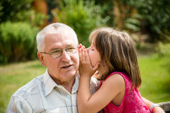 Tell me secret. Little girl whispering her grandfather a secret to ear - outdoor in backyard Stock Photos