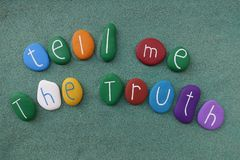 Tell me the truth, multicolored stones text over green sand Royalty Free Stock Photography