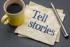 Tell stories advice or reminder on naokin. Tell stories advice or reminder - handwriting on a napkin with cup of espresso coffee against gray slate stone Stock Images