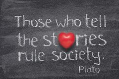 Tell stories heart. Who tell stories famous quote of ancient Greek philosopher Plato written on chalkboard with red heart symbol instead of O Stock Photos