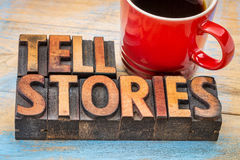 Tell stories words in wood type. Tell stories word abstract - text in vintage letterpress wood type with a cup of coffee - storytelling concept royalty free stock image