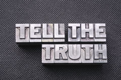 Tell the truth bm. Tell the truth phrase made from metallic letterpress blocks on black perforated surface royalty free stock photo
