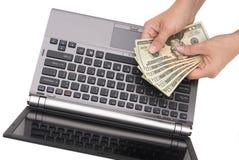 Tellend contant geld op laptop Stock Foto's
