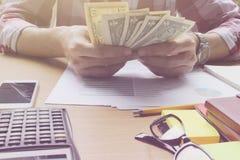 Tellend de dollargeld van het handgebruik op de bureauinvestering Stock Afbeelding