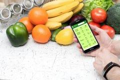 Tellende calorieën in smartphone stock foto