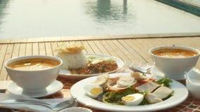 Teller der thail?ndischen K?che 4K Tabelle durch das Pool Thail?ndisches traditionelles Mittagessen durch das Pool stock video