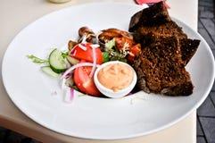 Teller der Tomaten und des Fleisches mit braunem Brot stockfotografie