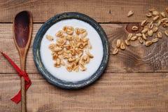 Teller des Getreides mit Milch und hölzernem Löffel Stockbilder