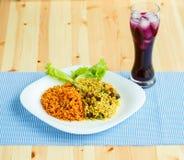 Teller gemacht von zwei Arten Reis auf einer weißen Platte und einem Glas von J Stockfotografie