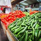 Teller met komkommers en tomaten in de markt Stock Foto's