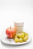 Teller mit Jogurt, Apfel und Trauben Lizenzfreies Stockfoto