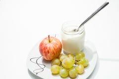 Teller mit Jogurt, Apfel und Trauben Stockfoto