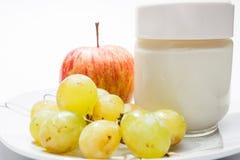 Teller mit Jogurt, Apfel und Trauben Stockfotos