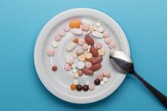 Teller mit Pillen auf einer Platte mit Löffel Stockfotos