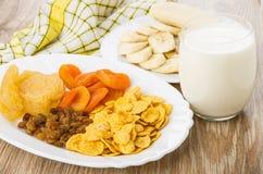 Teller mit Trockenfrüchten, Glasmilch, Scheiben von Bananen Lizenzfreies Stockbild