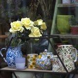 Teller und ein Vase Blumen im Fenster des Baumarkts, in dem Sie verschiedene gemütliche Sachen für die Verzierung des Hauses kauf Lizenzfreie Stockbilder