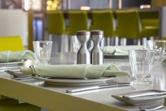 Teller und Gläser mit Serviette auf Speisetische Stockbild