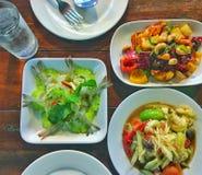 Teller von Hühner- und Acajounüssen und von würzigem Salat Stockbilder
