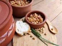 Teller von Kichererbsen mit Zwiebel, Tomaten und gebratenem Speck Stockbilder