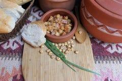 Teller von Kichererbsen mit Zwiebel, Tomaten und gebratenem Speck Lizenzfreies Stockfoto