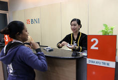 Teller. Was serving customers at a bank in the city of Solo, Central Java, Indonesia Stock Photo