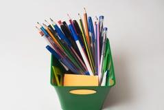 Tellers, pennen, potloden in een groene mand stock fotografie