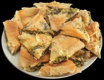 Tellervoll frisch Oven Baked Serbian Traditional Cheese-Spinats-Torte Zeljanica-Scheiben lokalisiert auf schwarzem Hintergrund stockbild
