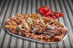 Tellervoll Spucken gebratene Schweinefleisch-Scheiben mit Bündel der Tomate auf altem Bambus-Mat Background Stockfotos